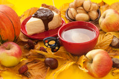 A  cup of tea, a piece of an appetizing cake with melted chocolate on it, a pumpkin, apples, autumn leaves and chestnuts Stock Photo
