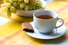 Cup of tea with a piece of biscuit and grapes. White cup of tea on saucer with a a piece of biscuit and grapes Stock Images