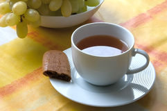 Cup of tea with a piece of biscuit and grapes. White cup of tea on saucer with a a piece of biscuit and grapes Royalty Free Stock Photography