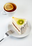 A cup of tea and a piece of creamy cake Stock Images