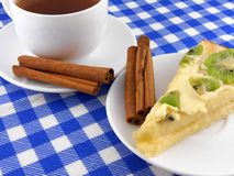 A cup of tea and a piece of tasty creamy cake with cinnamon Royalty Free Stock Images