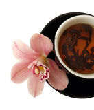 Cup of tea with pink orchids on black plate isolated Stock Photography