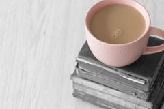 Cup of tea in a pink cup on a stack of old antique books with selective colour stock photography