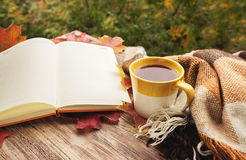 Cup of tea with plaid, leaves and notepad on the wood background Royalty Free Stock Image