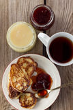 Cup of tea, plate of pancakes, jam, honey Stock Images