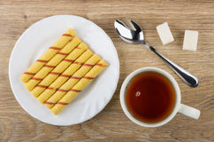 Cup of tea, plate with wafer rolls, teaspoon and sugar Royalty Free Stock Images
