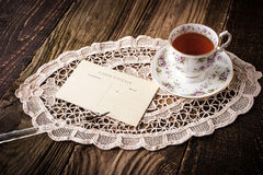 Cup of tea with postcard and pen  horizontal. Cup of tea with postcard and lace napkin and pen on the wooden table horizontal Stock Images