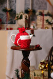 A cup and tea-pot is in New-year scenery. Decorated the knitted scarf and cap create the atmosphere of heat, comfort, holiday Stock Image