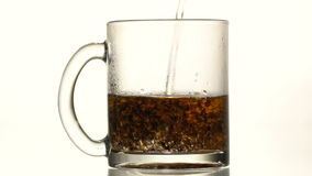 The cup of tea is poured boiling water. A glass cup of black tea, pour boiling water. Slow motion. Close-up stock footage