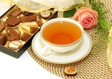 Cup of tea, pralines and pink rose - holiday compo Stock Images