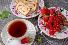 Cup of tea, raspberry with chocolate and biscuit roll stock photo
