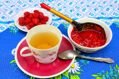 A cup of tea and raspberry jam. A cup of tea, fresh raspberries on a plate and Pialat with raspberry jam on a light background Royalty Free Stock Photo