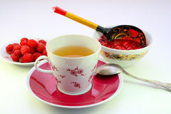 A cup of tea and raspberry jam. A cup of tea, fresh raspberries on a plate and Pialat with raspberry jam on a light background Stock Photos