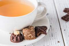Cup of tea with raw handmade chocolate candies on white wooden background Stock Images