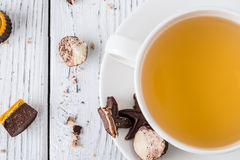 Cup of tea with raw handmade chocolate candies on white wooden background Royalty Free Stock Photos
