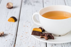 Cup of tea with raw handmade chocolate candies on white wooden table. Cup of tea with raw handmade chocolate candies on white wooden background. Healthy Royalty Free Stock Image