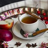 A cup of tea with red apples and cinnamon royalty free stock image