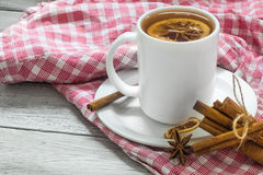 Cup of tea on a red tablecloth, beautiful white wooden background, cinnamon sticks, lemon and berries Stock Photos