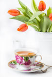 Cup of tea with red tulips over white Stock Image