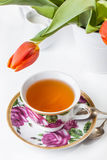 Cup of tea with red tulips over white Stock Images