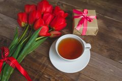 A cup of tea red tulips pattern and gift box on wooden background . . Valentines Day and Mother`s Day background . Stock Photography