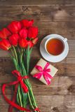 A cup of tea red tulips pattern and gift box on wooden background . . Valentines Day and Mother`s Day background . Royalty Free Stock Photo