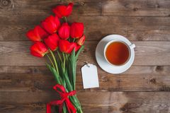 A cup of tea red tulips pattern and gift box on wooden background . . Valentines Day and Mother`s Day background . Stock Image