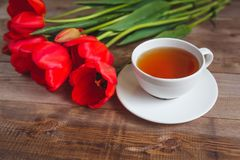 A cup of tea red tulips pattern on wooden background . Valentines Day and Mother`s Day background . Royalty Free Stock Images