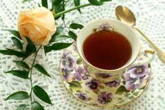 Cup of tea and rose on knitted table cover Stock Image