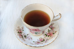 Cup of tea in a rose patterned china teacup and saucer Royalty Free Stock Image