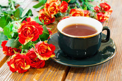 Cup of tea and roses bouquet on table Stock Photo