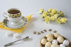Romantic yellow Easter scene with tea, Easter eggs, spoon and roses. royalty free stock photography