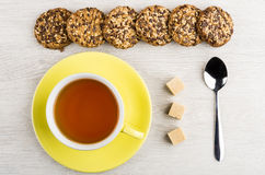 Cup of tea and row cookies, teaspoon and lump sugar Stock Photos