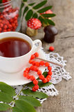 Cup of tea and rowan beads on a wooden table Stock Images