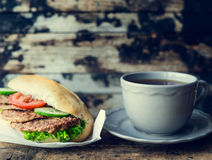 Cup of tea and a sandwich with meat on a dark wooden background , toned. Cup of tea and a sandwich with meat on dark wooden background , toned stock photo