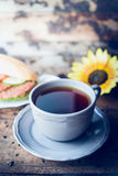 Cup of tea and a sandwich with meat on a dark wooden background , toned. Cup of tea and a sandwich with meat on dark wooden background , toned stock photography