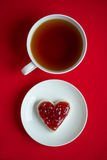 A cup of tea and a sandwich. In the shape of a heart with raspberry jam royalty free stock photo