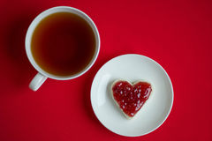 A cup of tea and a sandwich. In the shape of a heart with raspberry jam royalty free stock photography