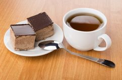 Cup of tea, saucer with cakes with chocolate and teaspoon Stock Photo