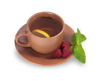 Cup of tea on a saucer with lemon, raspberry and mint leaves iso. Lated on white background Stock Photo