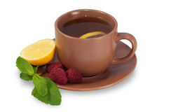 Cup of tea on a saucer with lemon, raspberry and mint leaves iso Stock Images