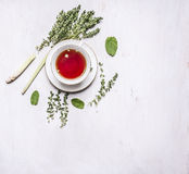 Cup of tea on a saucer with a set of herbal tea thyme, mint, lemon grass on wooden rustic background top view with text area, vint Stock Photography