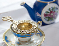 An cup of tea. With saucer, strainer and blue tea pot Royalty Free Stock Photos
