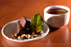 Cup of tea and saucer with sweet dessert stock photography