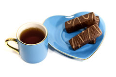 Cup with tea and a saucer with sweets Stock Photography