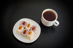 Cup of tea, saucer with Turkish Delight on a black table, top view.  Royalty Free Stock Photos
