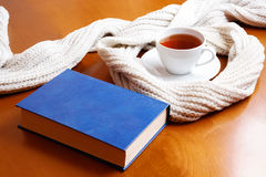 Cup of tea, scarf and book Stock Photos