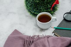 A cup of tea, a scarf, a magnifying glass, a pencil, a notebook and a small artificial Christmas tree against the background of sn royalty free stock photo