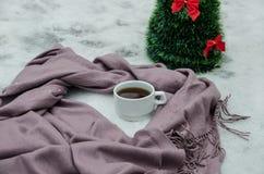 A cup of tea, a scarfand a small artificial Christmas tree stock photos