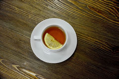 Cup of tea. Served with lemon, on wooden background. Shot made from above Stock Images
